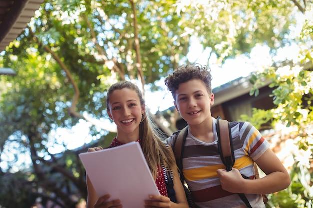 Porträt der glücklichen klassenkameraden, die buch halten