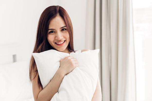 Porträt der glücklichen lächeln asiatischen frau genießen und entspannen auf dem bett im schlafzimmer zu hause.asiann schönheit