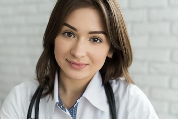 Porträt der glücklichen lächelnden ärztin mit stethoskop