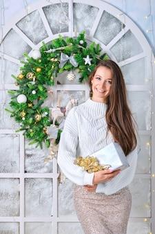 Porträt der glücklichen lächelnden dame mit geschenkbox in der hand