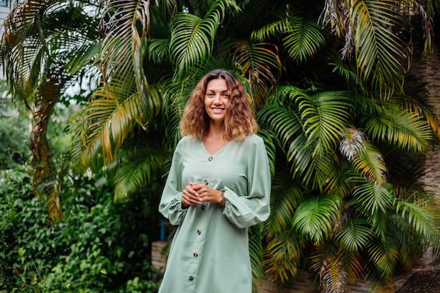 Porträt der glücklichen lächelnden europäischen gebräunten frau mit dem kurzen lockigen haar im sommerlichen romantischen langarmkleid außerhalb der villa