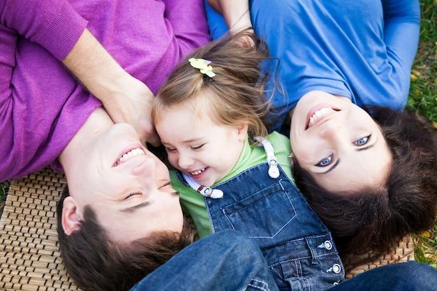 Porträt der glücklichen lächelnden familie, die draußen im herbstpark liegt?