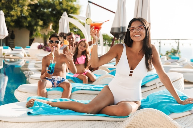 Porträt der glücklichen lächelnden familie mit kindern, die auf liegestühlen nahe dem schwimmbad außerhalb des hotels liegen und cocktails trinken