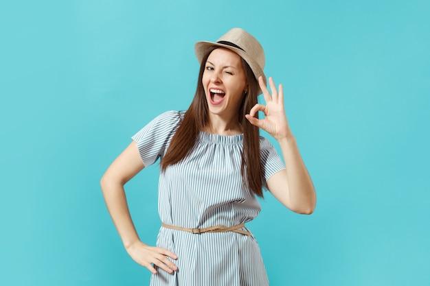 Porträt der glücklichen lächelnden frau, die kleid trägt, strohsommerhut, der ok geste zeigt, daumen signalisieren kopienraum lokalisiert auf blauem hintergrund. menschen aufrichtige emotionen, lifestyle-konzept. werbefläche.