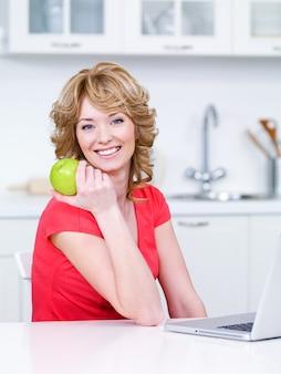 Porträt der glücklichen lächelnden frau mit grünem apfel, der in der küche sitzt