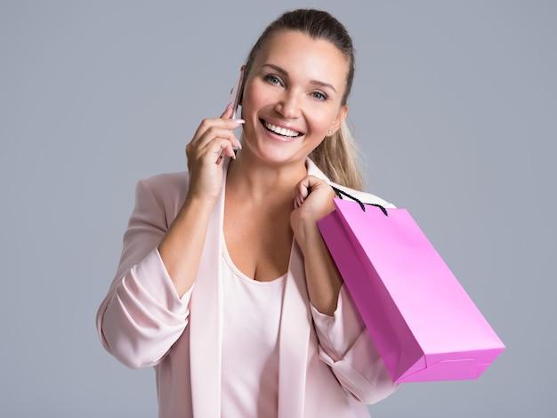 Porträt der glücklichen lächelnden frau mit rosa einkaufstasche, die auf einem handy spricht.