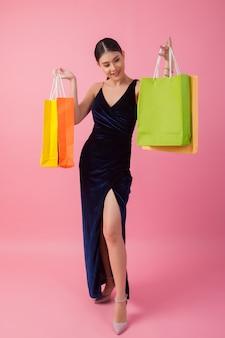 Porträt der glücklichen lächelnden frauengriffeinkaufstasche