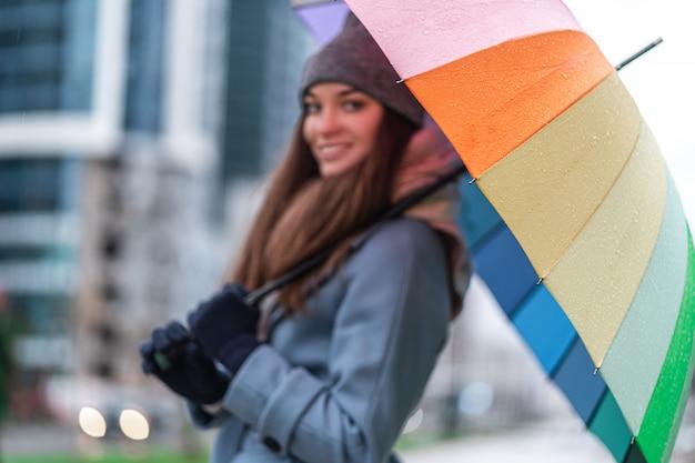 Porträt der glücklichen lächelnden freudigen frau in der warmen kleidung mit hellem mehrfarbigem regenbogenschirm