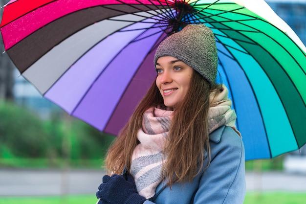 Porträt der glücklichen lächelnden freudigen sorglosen frau in der warmen kleidung mit hellem mehrfarbigem regenbogenschirm