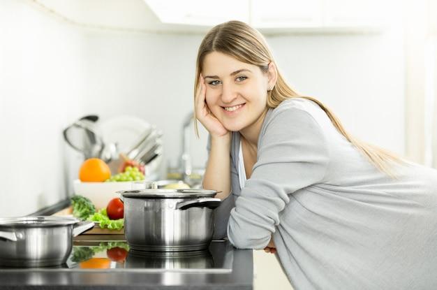 Porträt der glücklichen lächelnden hausfrau, die auf küche aufwirft und suppe kocht