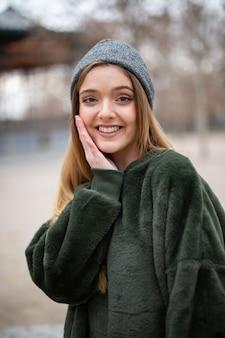 Porträt der glücklichen lächelnden jungen blonden frau mit winterhut in einem park im herbst