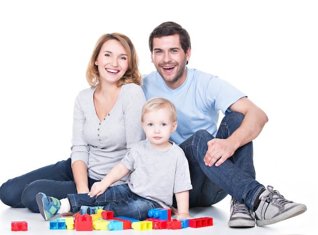 Porträt der glücklichen lächelnden jungen eltern, die mit einem baby spielen - lokalisiert auf weiß