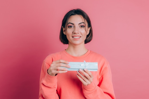 Porträt der glücklichen lächelnden mädchenöffnungsgeschenkbox lokalisiert auf rosa hintergrund