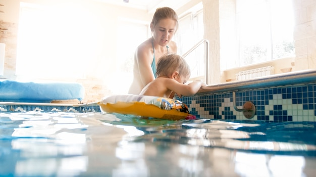 Porträt der glücklichen lächelnden mutter mit dem 3 jahre alten kleinen sohn, der im pool im fitnessstudio schwimmt. familie entspannen, spaß haben und im wasser spielen