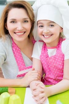 Porträt der glücklichen lächelnden mutter und der tochter in der rosa schürze an der küche