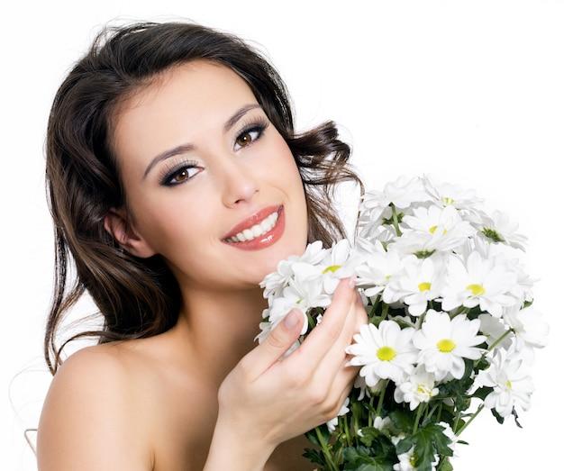 Porträt der glücklichen lächelnden schönen jungen frau mit blumenstraußblumen - lokalisiert auf weiß
