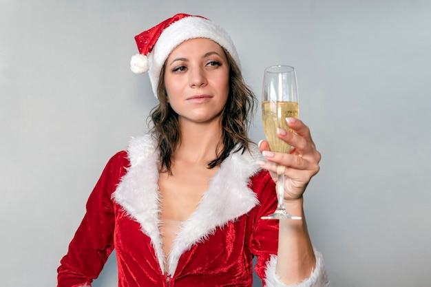 Porträt der glücklichen lächelnden schönen jungen weihnachtsfrau mit sankt-hut und glas champagner über grauem hintergrund