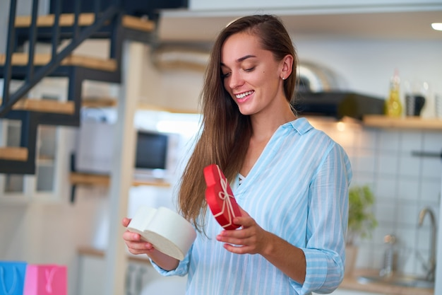 Porträt der glücklichen lächelnden zufriedenen niedlichen geliebten überraschten frau mit einer herzförmigen geschenkbox am valentinstag 14. februar