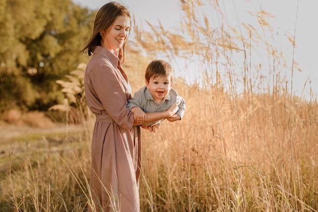 Porträt der glücklichen liebenden mutter, die ihren kleinen sohn im sonnigen park nahe fluss umarmt