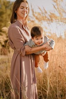 Porträt der glücklichen liebenden mutter, die ihren kleinen sohn im sonnigen park nahe fluss umarmt.