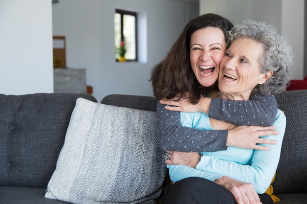 Porträt der glücklichen mittleren erwachsenen frau, die ihre ältere mutter umfasst