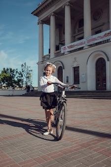 Porträt der glücklichen modekleinkinder, die spaß mit fahrrad in der stadt haben.