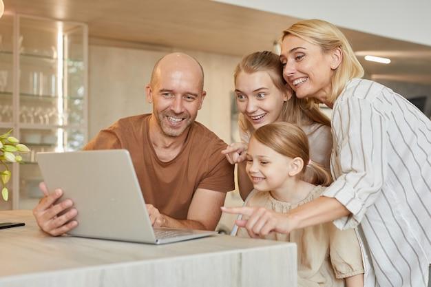 Porträt der glücklichen modernen familie, die laptop zusammen benutzt, während sie durch video-chat mit verwandten in gemütlichem wohnraum spricht