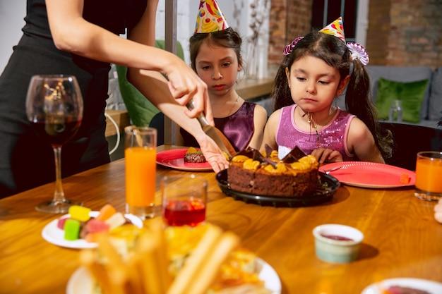 Porträt der glücklichen multiethnischen familie, die einen geburtstag zu hause feiert. große familie, die kuchen isst und wein trinkt, während sie grüßt und lustige kinder hat. feier, familie, party, hauptkonzept.