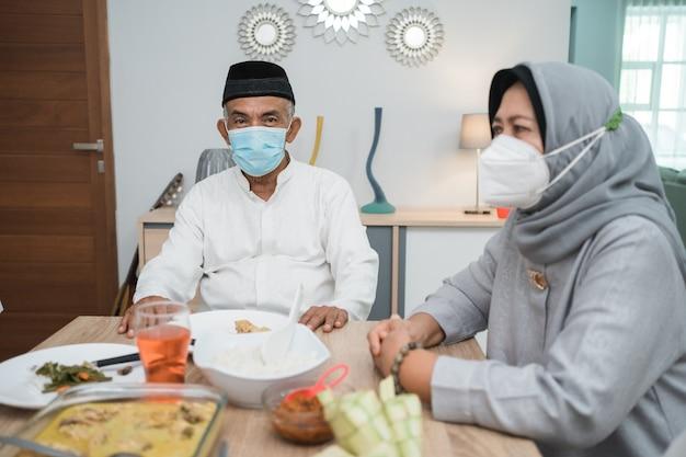 Porträt der glücklichen muslimischen familie tragen maske während der eid mubarak feier zu hause