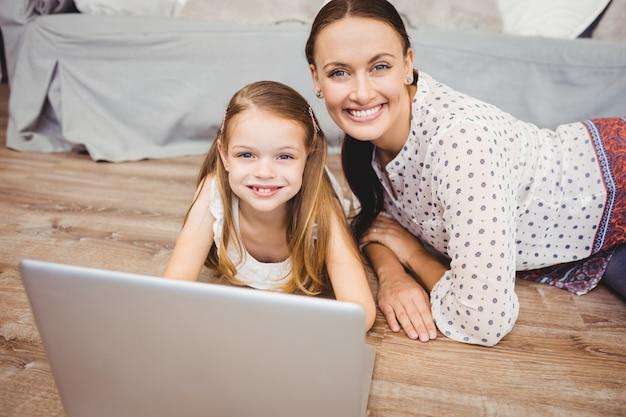 Porträt der glücklichen mutter und der tochter mit laptop