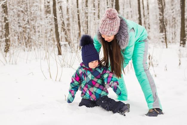 Porträt der glücklichen mutter und des babys im winterpark