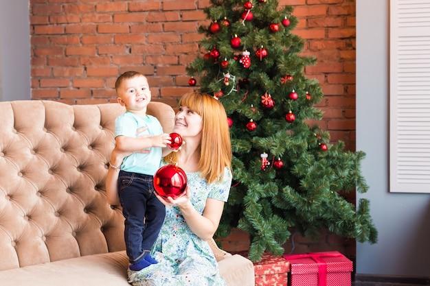 Porträt der glücklichen mutter und des lachenden babys, das kugel gegen festlichen innenraum mit hält