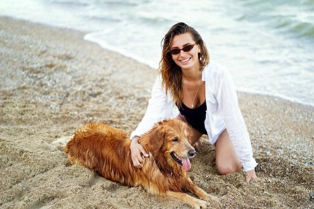 Porträt der glücklichen niedlichen jungen frau, die ihren hund sitzt und umarmt