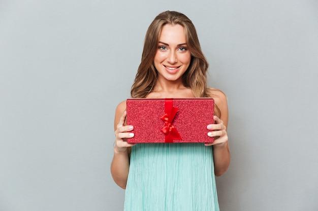 Porträt der glücklichen niedlichen jungen frau mit geschenkbox über grauer wand