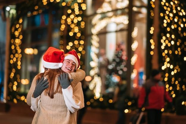 Porträt der glücklichen niedlichen jungen freunde, die einander umarmen und lächeln, während sie am heiligabend im freien gehen.