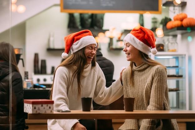Porträt der glücklichen niedlichen jungen freunde, die spaß im café haben