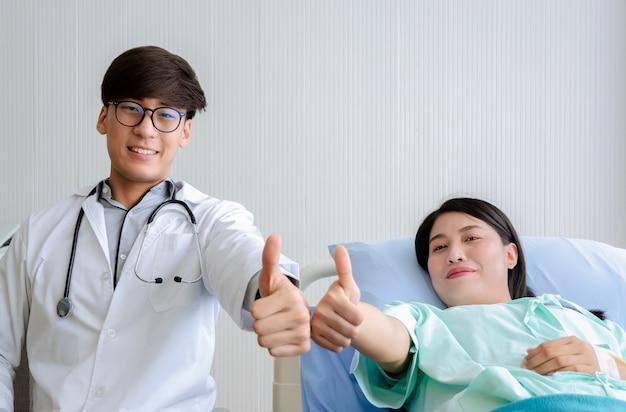 Porträt der glücklichen patientin, die auf krankenhausbett und männlichem arzt liegt, zeigt daumen hoch zeichen. gesundheits- und versicherungskonzept