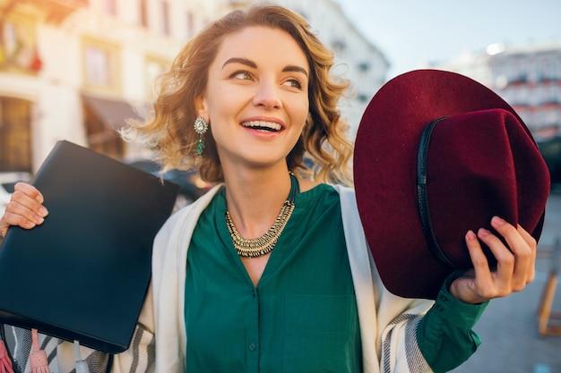 Porträt der glücklichen positiven frau, die offen lächelt, frühlingsmode-straßenstil, grüne blose tragend
