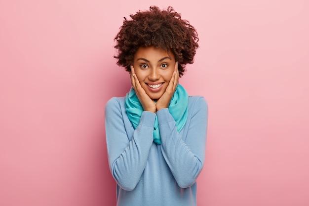 Porträt der glücklichen positiven frau mit natürlichem klarem haar, berührt wangen