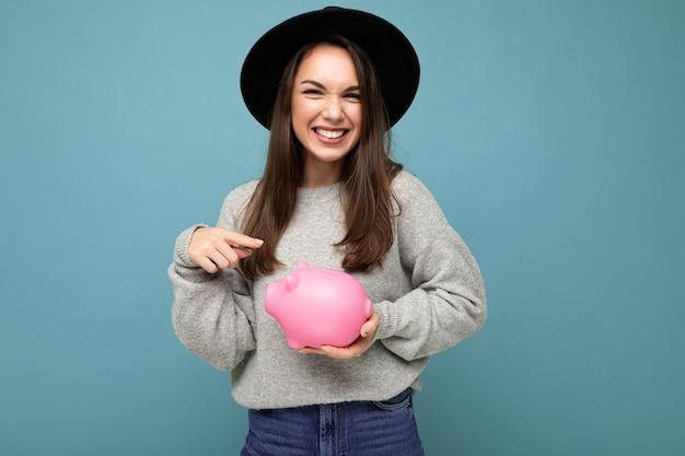 Porträt der glücklichen positiven lächelnden jungen schönen brunettefrau, die stilvolle graue strickjacke trägt und