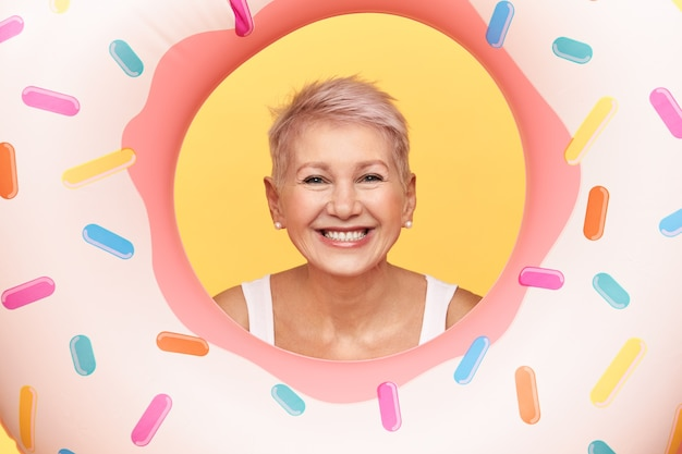 Porträt der glücklichen positiven reifen frau mit der kurzen frisur, die kopf heraus in loch des aufblasbaren rosa donuts herausragt, spaß am strand hat, schwimmt, breit lächelt.