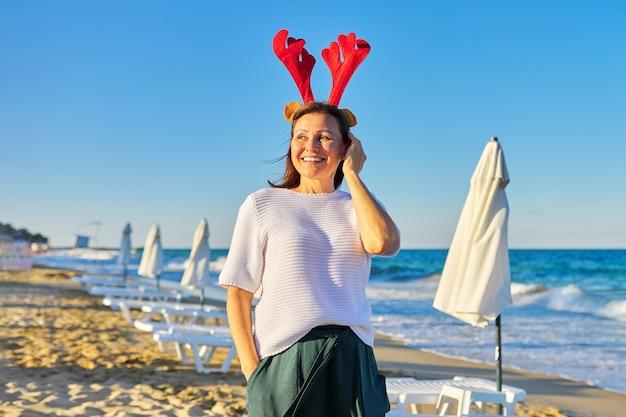 Porträt der glücklichen reifen frau in den ferienohren am strand