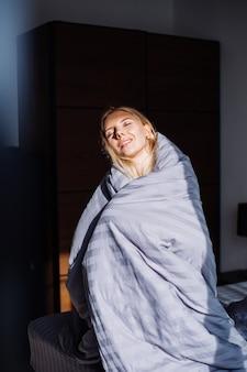 Porträt der glücklichen ruhigen frau im schlafzimmer in der grau abgestreiften decke und im schwarzen und beigen körper, schlafanzug zu hause