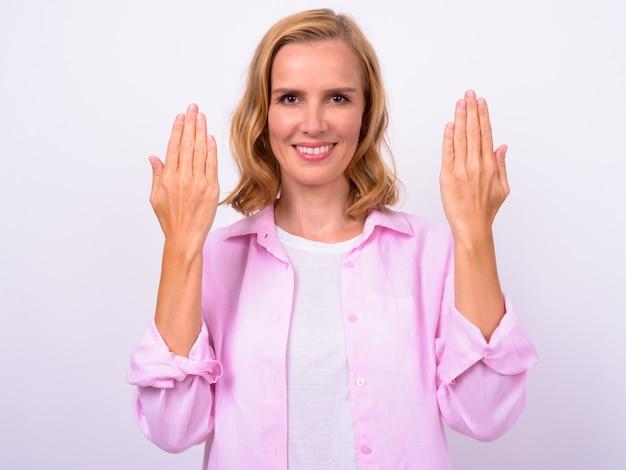 Porträt der glücklichen schönen blonden frau, die handrücken zeigt