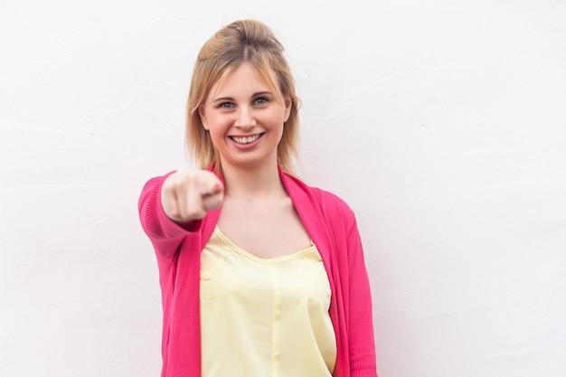 Porträt der glücklichen schönen blonden jungen frau im gelben hemd und in der roten bluse, die mit einem zahnigen lächeln steht, zeigt und kamera betrachtet. indoor-studioaufnahme, isoliert auf weißem wandhintergrund.