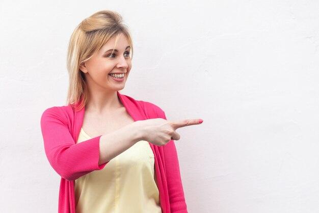 Porträt der glücklichen schönen blonden jungen frau in gelbem hemd und roter bluse, die mit glücklichem gesicht und zahnigem lächeln steht, zeigt und exemplar zeigt. studioaufnahme, isoliert auf weißem wandhintergrund.