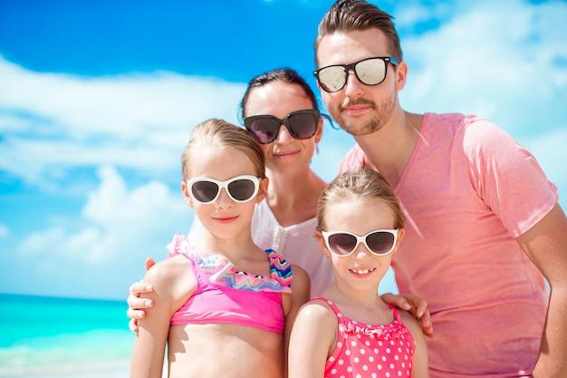 Porträt der glücklichen schönen familie auf weißem strand
