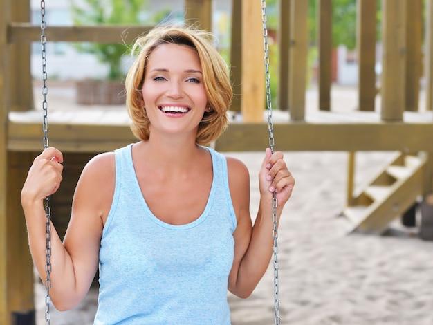 Porträt der glücklichen schönen frau, die spaß auf einer schaukel in einem sommerpark hat.