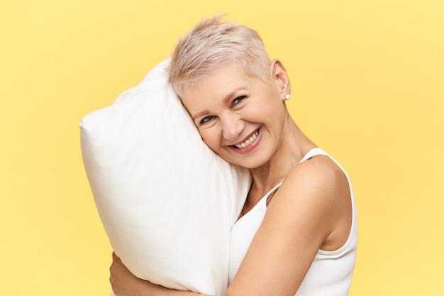 Porträt der glücklichen schönen frau mittleren alters mit hemdhaar, das energetischen blick wegen des vollen nachtschlafes auf bequemem weißem gedächtnisschaumkissen hat.