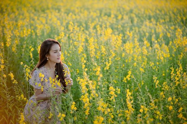 Porträt der glücklichen schönen glücklichen jungen frau, die im park entspannt. frau in einem gelben blumengarten.